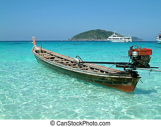 longtail motor boat moored in blue tropical waters, similan...