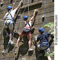 Three climbers photographed on a ropes course during a...