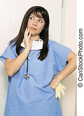 Assumption - Nurse standing with hand on hip and thinking or...