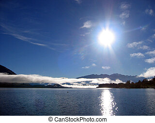 Bright sun and lake - Long white cloud, lake and sun