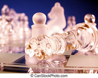 game over - king down in defeat in focus on chess board