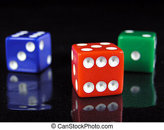 red, green, and blue dice on a reflective black surface.