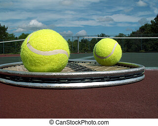 tennis balls and racket - tennis racket and two balls lying...