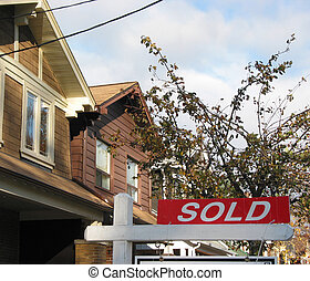 Sold - Residential street with a sold sign near one of the...
