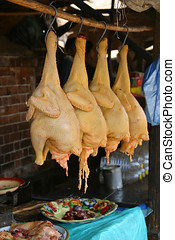 Chickens for sale - Four skinny chickens hanging for sale at...