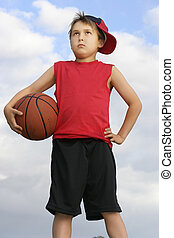 Standing child holding a basketball - Boy in a red shirt and...