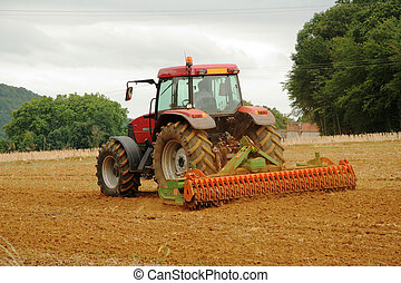 French Tractor Ploughing - Red Tractor in Wheat field