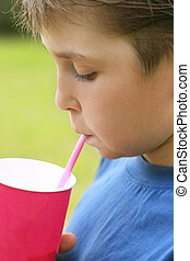Sipping a milkshake - Child drinks a milkshake from a...