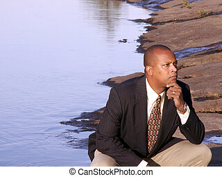 thinking - business man in a suit squatting down thinking