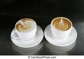 Cappucinno with Latte Art - Two single cappuccinos sitting...