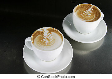 Cappucinno with Latte Art - Two single cappuccino's sitting...