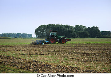 Agricultural works - Tractor plowing the field