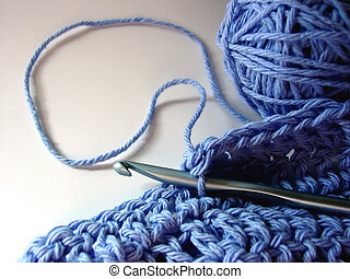Crocheting - Blue yarn and a crochet hook are working on a...