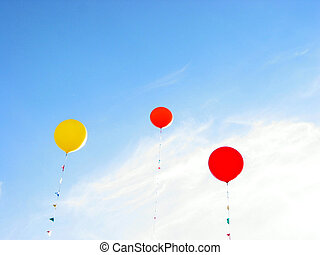 Colorful balloons flying in blue sky on a bright summer day