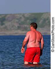 Sunburn Alert - Overweight man wearing bright red swimming...