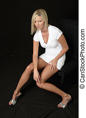 Attractive blonde in white dress sitting over black...