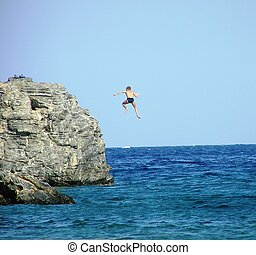 jumping off cliff - a boy jumping off a high cliff, into the...
