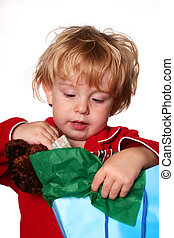Opening Presents - young boy opening a gift bag