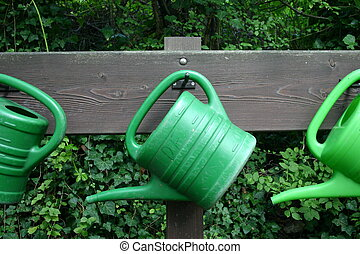 Watering cans - Three green watering cans at a wooden board