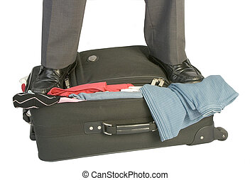 overfilled suitcase with male legs pressing lid closed
