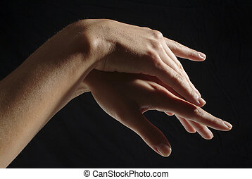 Woman hands, manicured, on black background
