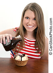 Ice Cream Sundae - Young teen girl pouring chocolate sauce...