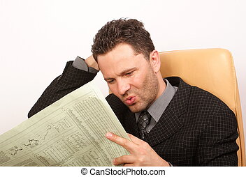bad news - worried handsome business man reading newspaper -...