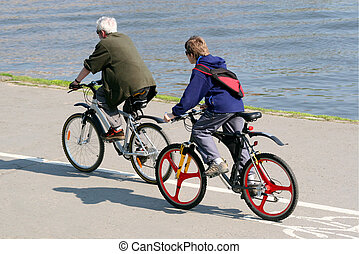 family on bicycles - Father and son are riding on mountain...
