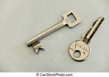 two keys - pair of different shaped keys on grey surface