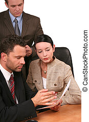 Business team - 3 people reading report at the desk -...