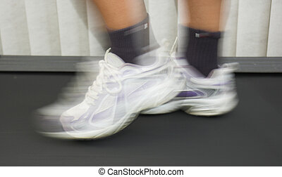 Blurred workout - Hard working feet on treadmill. Blur...