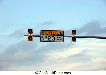 School zone sign with sky in background
