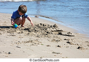 Child at the beach - Young boy playing and digging at the...