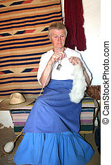 Spinning - Woman spinning wool into yarn using drop spindle
