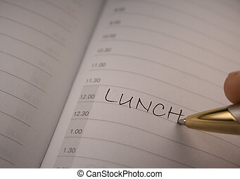 pen writing in diary - pen with lunch in focus