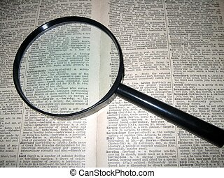 Magnifying glass on old dictionary