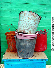 Rusty Buckets - A set of rusty buckets over a wooden wall