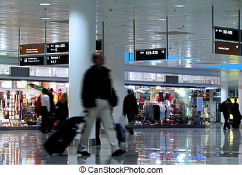 Walking in an airport - Man with suitcase walking in an...