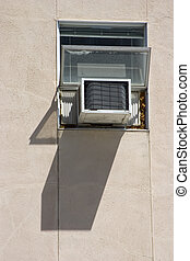 Window Air Conditioner - An air conditioner hangs outside of...