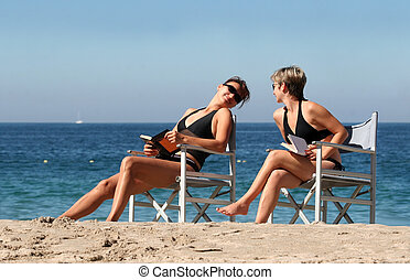 2 women on the beach - 2 women reading on the beach