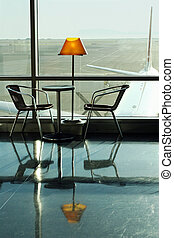 Cafe at the airport - Table, lamp and 2 chairs at the...