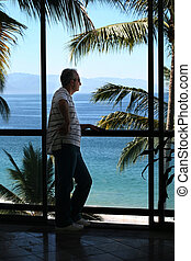 Man by the window - Man standing by the window in a tropical...