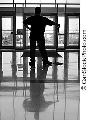 Reflection - a silhouette of a man resting after mopping the...