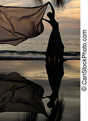 Woman with a scarf and her reflection in a pool by the ocean