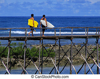 Surfers underway to action - Surfers with surfboard on their...
