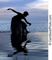 Reflection - Woman and her reflection in a pool by the ocean