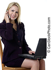 Attractive business woman working on laptop and talking on...