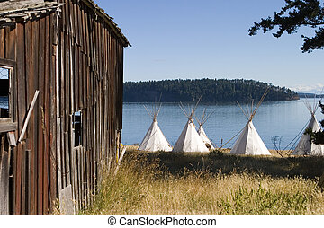 Old Barn and Teepees - A group of teepees located next to an...