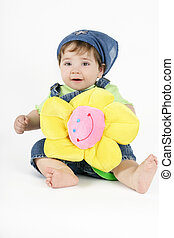 Country Bumpkin - A baby in a denim outfit holds a yellow...