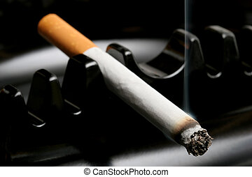 cigarette smoking in ashtray - cigarette smoking away in a...